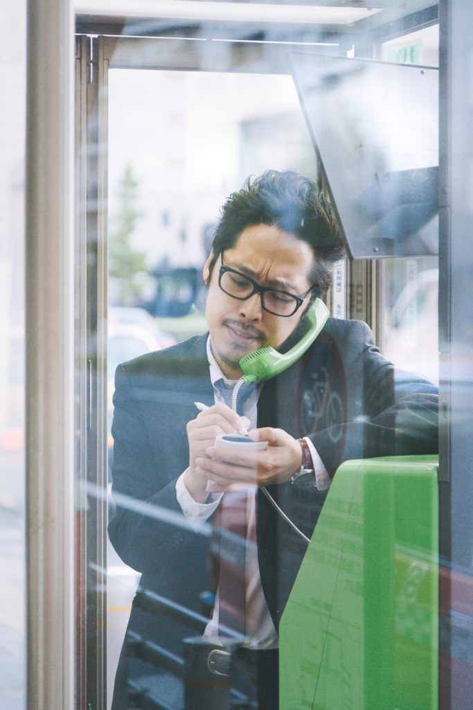 公衆電話で話すビジネスマン