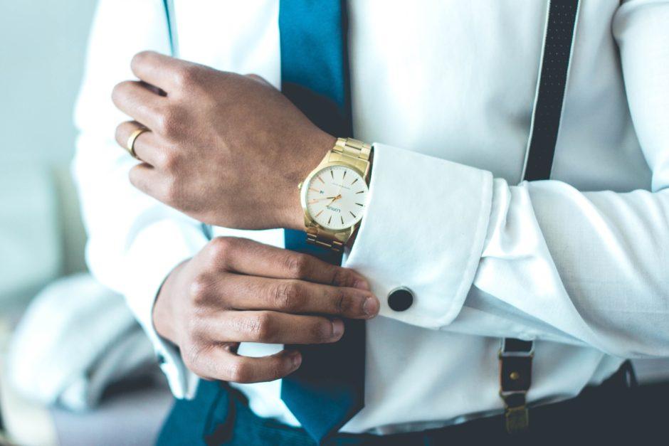 ワイシャツの袖ボタンを止めるビジネスマン