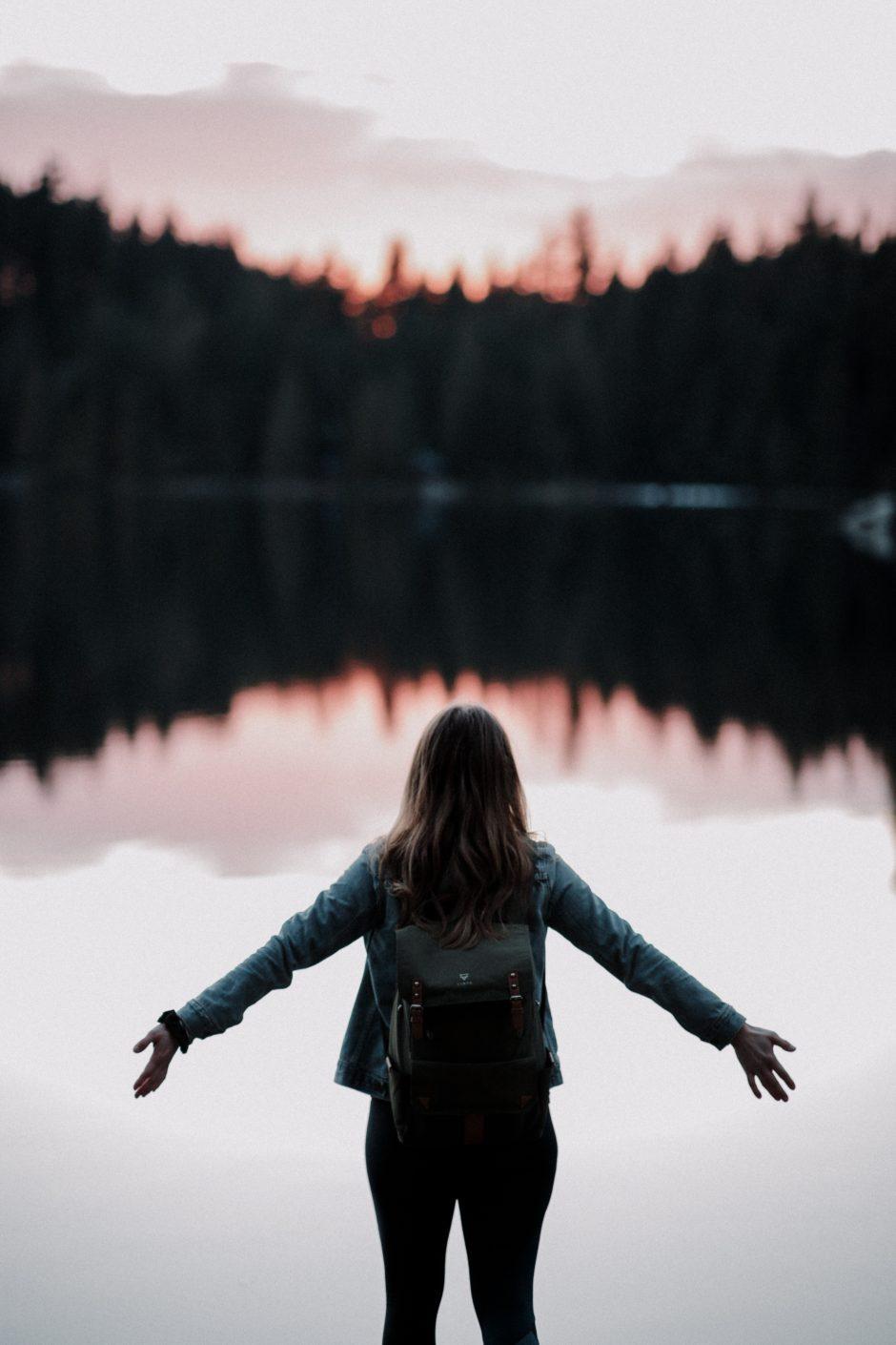 湖に手を広げる女性